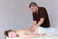 Śliczny męski masażu terapeuta robi wznawiać procedurę dla plecy Zdjęcie Royalty Free