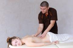 Śliczny męski masażu terapeuta robi wznawiać procedurę dla plecy Zdjęcie Stock