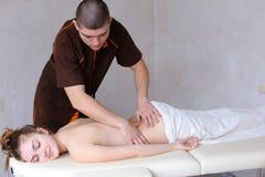Śliczny męski masażu terapeuta robi wznawiać procedurę dla plecy Obraz Royalty Free