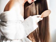 Śliczny, młoda kobieta czesze jej włosy Obrazy Stock