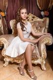 Śliczny młodej dziewczyny obsiadanie na krześle Zdjęcia Royalty Free