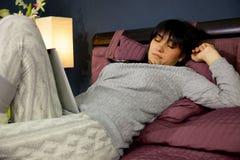 Śliczny młodej kobiety dosypianie z pastylką na twój nodze w sypialni Zdjęcia Royalty Free