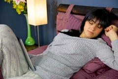 Śliczny młodej kobiety dosypianie z pastylką na twój nodze w sypialni zbliżeniu Zdjęcie Royalty Free