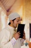 Śliczny młody arabski facet modli się bóg z świętą księgą w jego ręki Fotografia Stock