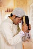 Śliczny młody arabski facet modli się bóg z świętą księgą w jego ręki Fotografia Royalty Free
