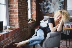 Śliczny młody uśmiechnięty kobiety obsiadanie na krześle w domu zdjęcia stock