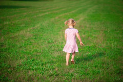 Śliczny mała dziewczynka bieg przy trawy łąką Obrazy Royalty Free