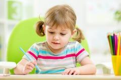 Śliczny mała dziewczynka rysunek z colourful ołówkami Fotografia Stock