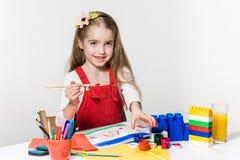 Śliczny mała dziewczynka rysunek z farbą i paintbrush w domu Obrazy Royalty Free