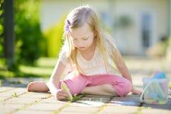 Śliczny mała dziewczynka rysunek z kolorowym pisze kredą na chodniczku Lato aktywność dla małych dzieciaków Fotografia Stock