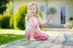 Śliczny mała dziewczynka rysunek z kolorowym pisze kredą na chodniczku Lato aktywność dla małych dzieciaków Obrazy Royalty Free