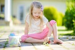 Śliczny mała dziewczynka rysunek z kolorowym pisze kredą na chodniczku Lato aktywność dla małych dzieciaków Obraz Stock