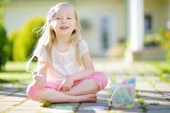 Śliczny mała dziewczynka rysunek z kolorowym pisze kredą na chodniczku Lato aktywność dla małych dzieciaków Zdjęcie Stock