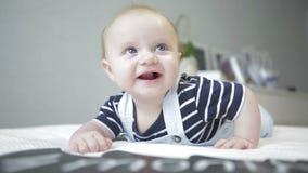Śliczny małe dziecko jest łgarski na żołądku i patrzeć w kamerę zbiory wideo