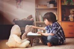 Śliczny małe dziecko, preschool chłopiec, czyta książkę jego miś pluszowy był Zdjęcia Royalty Free