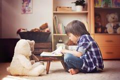 Śliczny małe dziecko, preschool chłopiec, czyta książkę jego miś pluszowy był Obrazy Stock