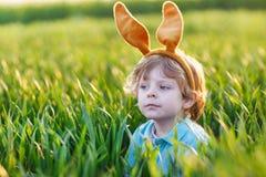 Śliczny małe dziecko z Wielkanocnego królika ucho bawić się w zielonej trawie Fotografia Stock
