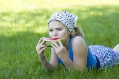 Śliczny małej dziewczynki łasowania arbuz na trawie Zdjęcie Stock