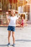 Śliczny małej dziewczynki łasowania cukierku jabłko i pozować przy jarmarkiem w parku rozrywki obrazy royalty free