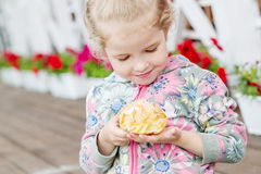 Śliczny małej dziewczynki łasowania eclair Zdjęcia Royalty Free