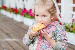 Śliczny małej dziewczynki łasowania eclair Obraz Royalty Free