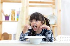 Śliczny małej dziewczynki łasowania zboże z mlekiem zdjęcie royalty free