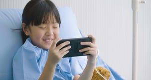 Śliczny małej dziewczynki lying on the beach na łóżku w szpitalu, dopatrywanie śmieszne kreskówki, filmy na smartphone Choroba i  zbiory wideo