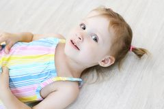 Śliczny małej dziewczynki lying on the beach na podłoga w dziecka ` s pokoju zdjęcia royalty free