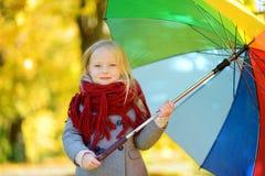 Śliczny małej dziewczynki mienia tęczy parasol na pięknym jesień dniu Szczęśliwy dziecko bawić się w jesień parku Fotografia Royalty Free