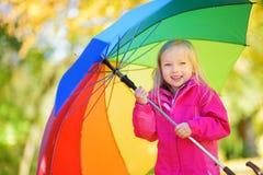 Śliczny małej dziewczynki mienia tęczy parasol na pięknym jesień dniu Szczęśliwy dziecko bawić się w jesień parku Zdjęcie Royalty Free
