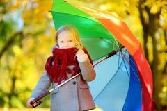 Śliczny małej dziewczynki mienia tęczy parasol na pięknym jesień dniu Szczęśliwy dziecko bawić się w jesień parku Obrazy Royalty Free