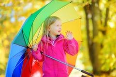 Śliczny małej dziewczynki mienia tęczy parasol na pięknym jesień dniu Szczęśliwy dziecko bawić się w jesień parku Fotografia Stock