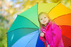 Śliczny małej dziewczynki mienia tęczy parasol na pięknym jesień dniu Szczęśliwy dziecko bawić się w jesień parku Zdjęcie Stock