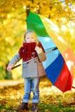Śliczny małej dziewczynki mienia tęczy parasol na pięknym jesień dniu Szczęśliwy dziecko bawić się w jesień parku Zdjęcia Royalty Free