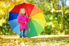 Śliczny małej dziewczynki mienia tęczy parasol na pięknym jesień dniu Szczęśliwy dziecko bawić się w jesień parku Obraz Royalty Free