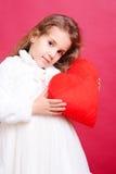 Śliczny małej dziewczynki mienia valentine serce na czerwieni Fotografia Stock