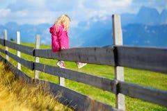 Śliczny małej dziewczynki obsiadanie na drewnianym ogrodzeniu podziwia pięknego krajobraz w dolomitu pasmie górskim Fotografia Royalty Free