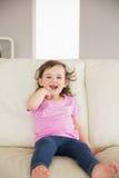 Śliczny małej dziewczynki obsiadanie na kanapie w domu fotografia royalty free