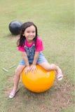 Śliczny małej dziewczynki obsiadanie na wielkiej żółtej piłce Fotografia Stock