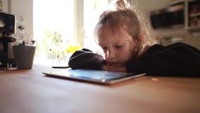 Śliczny małej dziewczynki obsiadanie przy stołem blisko dopatrywanie kreskówki na pastylka komputerze i okno, kładzenie głowa na  zdjęcie wideo