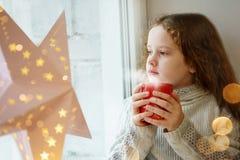 Śliczny małej dziewczynki obsiadanie z filiżanką gorący kakao okno a fotografia royalty free