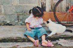 Śliczny małej dziewczynki obsiadanie z kotem zdjęcia royalty free