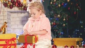 Śliczny małej dziewczynki odpakowania prezenta pudełko blisko dekorującej choinki, zdjęcie wideo