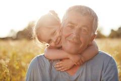 Śliczny mały żeński dzieciak z delikatnym uśmiechem obejmuje jej dziadu, radosnych wyrażenia, cieszy się, więź i słonecznego dzie obrazy stock