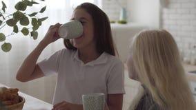 Śliczny mały albinos dziewczyn pić herbaciany i patrzeć each inny śmiać się w domu Poj?cie przyja?? Beztroski zbiory