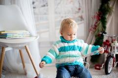 Śliczny mały berbecia dziecko z kolorową książką na śnieżnym zima dniu w domu obraz royalty free