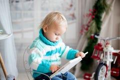 Śliczny mały berbecia dziecko z kolorową książką na śnieżnym zima dniu w domu zdjęcie stock
