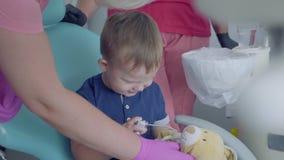 Śliczny mały dziecko bawić się z medycznymi narzędziami siedzi w krześle w dentysty biurze Beztroski dziecko odwiedza lekarkę zbiory wideo