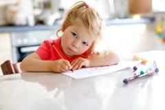 Śliczny mały dziecko berbecia dziewczyny obraz z kolorowymi ołówkami w domu Uroczy zdrowy szczęśliwy dziecko uczenie rysunek obok fotografia stock