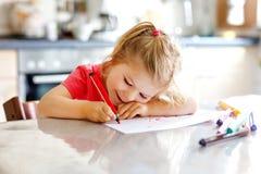 Śliczny mały dziecko berbecia dziewczyny obraz z kolorowymi ołówkami w domu Uroczy zdrowy szczęśliwy dziecko uczenie rysunek obok zdjęcie stock